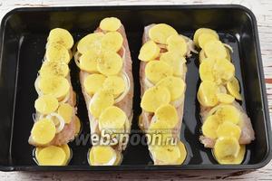 На лук выложить полосками кружочки картофеля. Эти кружочки должны быть очень тонкими (1-2 мм). Посыпать картофель оставшейся солью и чёрным молотым перцем. Готовить в предварительно разогретой до 170°C духовке приблизительно 35-40 минут (попробовать готовность картофеля).