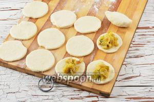На каждый кружок теста выложить 1 столовую ложку капустной начинки. Залепить пирожки и выложить их швом вниз.