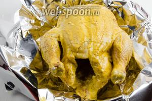 По глубокому сотейнику разложить фольгу для запекания в 2 слоя. Подготовленную курицу вынуть из холодильника, пакет снять с тушки. Выложить на фольгу. Завернуть края фольги. Поставить сотейник с тушкой в горячую духовку. Запекать курицу в течение 1 часа 30 минут под фольгой при температуре 180°C. Потом раскрыть фольгу и продолжить запекание курицы ещё 30 минут для получения румяной корочки. При этом пару раз стоит поливать тушку соусом, который собрался на дне сотейника. Общее время запекания 2 часа.