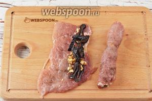 На один край (длинный) каждого промаринованного куска мяса выкладывать немного чернослива и грецких орехов. Завернуть каждый кусок рулетиком и выложить швом вниз.