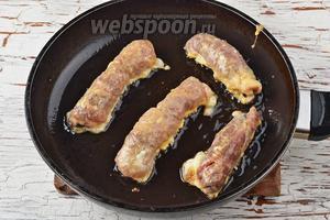 Выкладывать рулетики на сковороду с хорошо разогретым маслом (5 ст. л.). Обжарить со всех сторон до золотистой корочки.