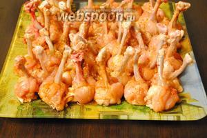 Смазать подготовленные крылья маринадом, выложить на блюдо, накрыть плёнкой и оставить для маринования на некоторое время.