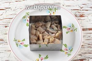 На блюдо выложить квадратную рамку (можно круглую) для формовки салатов. На дно выложить нарезанную кусочками селёдку (200 г).