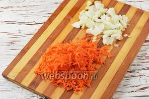 Лук (1 штуку) и 1 морковь очистить. Лук нарезать небольшими кубиками, а морковь натереть на крупной тёрке. Отправить овощи в сковороду с подсолнечным маслом (2 ст. л.) и жарить, помешивая, 5-6 минут.
