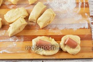 Разделить тесто на небольшие кусочки и распластать в лепёшку. Снять плёночку с сосисок (250 г) и нарезать их на кусочки. Выложить кусочки сосисок на середину лепёшки. Сформировать пирожки.