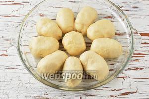Форму смазать подсолнечным маслом (5 мл). Выложить пирожки в форму. Накрыть полотенцем и дать подойти в тёплом месте 20-25 минут.