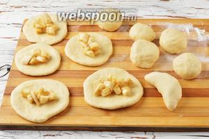 Из каждого кусочка теста сформировать лепёшку толщиной  0,5 сантиметра. На середину лепёшки выложить 1 столовую ложку банановой начинки. Сформировать пирожки, защипнув края.