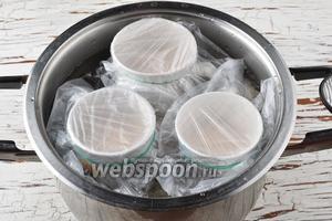 На дно кастрюли выложить ткань. Выложить на ткань кружки с фаршем. Заполнить кастрюлю холодной водой таким образом, чтобы вода доходила до половины кружек или немного выше. Замотать горлышко кружек пищевой плёнкой, чтобы во время варки туда не попала вода. Накрыть крышкой, довести до кипения и готовить после закипания 35-40 минут.