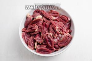 Пока варятся грибы, подготовить куриные сердечки (500 г). Куриные сердечки вымыть. Срезать верхнюю часть сердечка, разрезать его пополам, убрать запекшуюся кровь, ещё раз промыть. Просушить куриные сердечки на салфетке.