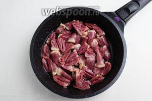 Нагреть сковороду с подсолнечным маслом (2 ст.л.). На сковороду выложить подготовленные куриные сердечки. Тушить их в течение 15 минут.