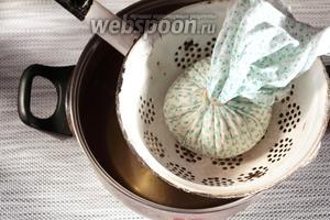 Откинуть соевый творог на дуршлаг, застеленный плотной тканью. Ткань можно использовать ту же, которая применялась при процеживании соевого молока, только её необходимо ополоснуть от остатков жмыха, чтобы они не попали в Тофу. Ткань достаточно хорошо отжать, полностью сушить не нужно. Собрать ткань с творогом в узелок и подвесить, чтобы стекла оставшаяся сыворотка. Но сыворотка должна будет ещё капать, сильно творог не «сушите».
