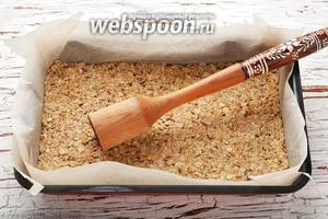 Форму (размером 20х30 сантиметров) выложить пекарской бумагой. Распределить овсяную смесь в форме и хорошо утрамбовать.
