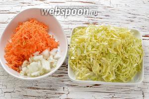 1 морковь и 1 луковицу очистить. Морковь натереть на крупной тёрке, лук нарезать мелким кубиком, капусту очень мелко нашинковать (лучше воспользоваться для этого специальной тёркой). Капусту соединить с солью(0,75 ч. л.), помять.