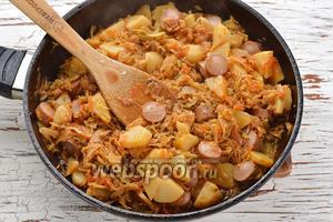 Тушёная капуста с картошкой и сосисками на сковороде готова.