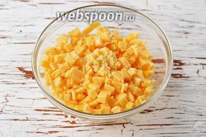 В миске соединить сыр и кукурузу. Добавить очищенный и пропущенный через пресс чеснок (2 зубчика).