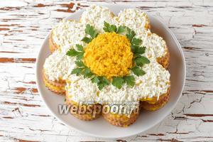 Отставленное 1 яйцо разделить на белок и желток. Натереть их по отдельности на мелкой тёрке. Выложить желток посредине, а белок — по краям, формируя «ромашку». Украсить свежей петрушкой (15 г). Отправить салат-торт в холодильник на 1 час.