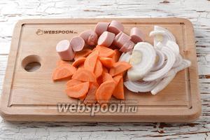 5 сосисок освободить от оболочки и нарезать небольшими кусочками. 1 морковь очистить и нарезать тонкими полукружочками. 1 Лук очистить и нарезать полукольцами.