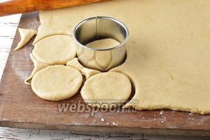 Раскатать тесто на слегка подпылённой мукой доске, толщиной 0,6 см. Вырезать кружки диаметром 8 сантиметров.