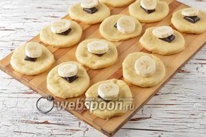 На середину каждого кружка выложить 1 дольку шоколада, а сверху — 1 кружок банана.