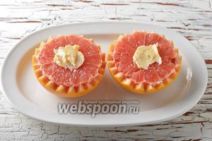 В центр грейпфрута выложить мягкое сливочное масло (5 г) и немного размазать (по вашему желанию этот шаг можно пропустить и масло не добавлять).