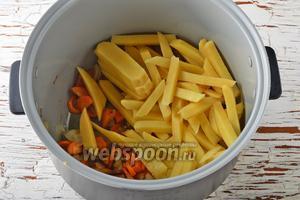 В чашу мультиварки (у меня мультиварка Polaris) выложить лук, морковь и подсолнечное масло. Включить мультиварку на режим «Жарка» и готовить, помешивая, 3-4 минуты. Затем добавить картофель, перемешать и готовить, помешивая, 2-3 минуты.