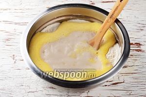 В большую миску 3 раза просеять муку (500 г). 1 столовую ложку муки отложить для обваливания изюма. Посредине сделать лунку. Вылить в лунку остальное тёплое молоко (150 мл), подготовленные яйца, дрожжи.