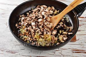 Добавить очищенные и мелко нарезанные шампиньоны (200 г). Жарить, помешивая, на огне ниже среднего, 5-6 минут.