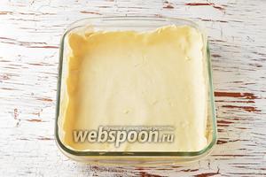 Охлаждённое тесто вынуть из холодильника и разделить на 2 части: 2/5 и 3/5. Большую часть тонко раскатать (очень легко раскатывать тесто между 2 листами пищевой плёнки) и выложить в форму размером 18х18 сантиметров, не забыв сформировать бортики. На дно формы не забудьте предварительно выложить пергаментную бумагу.