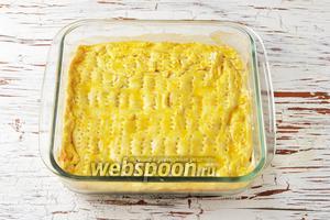 Сверху на начинку выложить раскатанную меньшую часть теста. Защипнуть края. Смазать тесто сверху отставленной яичной смесью (1 ст. л.) и часто поколоть вилкой.