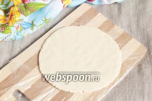 «Отдохнувшее» тесто попробуйте раскатать скалкой в тонкую лепёшку на подпылённой пшеничной мукой поверхности. Если раскатывается — отлично! Если возникнут сложности, то не паникуйте, всё у вас получится, но дело сноровки! Разделочную досочку застелить пищевой плёнкой и расплюснуть шарик в тонкую лепёшку руками, при необходимости макая пальцы в муку. Перевернуть досочку на свободную руку, придерживая ею лепёшку, аккуратно подцепив лепёшку, опустить её на руку, аккуратно выложить лепёшку на разогретую сухую сковороду. Жарить лепёшки с двух сторон.