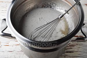 Поместить миску на паровую баню (дно миски не должно касаться кипящей воды ). Слегка мешать смесь венчиком, пока не растворится весь сахар, а смесь не нагреется до 60°С.