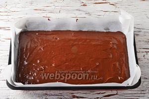 Форму (размером 22х32 сантиметра) выложить пергаментом. Вылить тесто в форму и разровнять. Выпекать в предварительно разогретой до 180°С духовке до готовности коржа (до сухой лучинки), приблизительно 35-40 минут. Вынуть корж, остудить, снять пергамент.