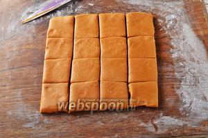 На слегка подпылённой мукой доске раскатать тесто толщиной 1-1,5 сантиметра. Нарезать тесто на квадратики. В этом рецепте лучше тесто нарезать ножом, а не формировать пряники с помощью различных формочек для вырезания печенья. Тогда пряники получатся более нежными.