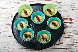 В небольшие формочки для кексов выложить по 1 столовой ложке теста. В центр воткнуть по 2 дольки шоколада.