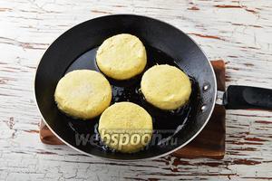 В сковороде разогреть подсолнечное масло 2 ст. л. Выложить сырники на горячую сковороду. Накрыть сковороду крышкой. Обжаривать сырники на умеренном огне до румяной корочки.