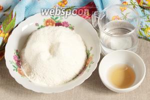 Для теста смешать 200 мл воды и 2 столовые ложки уксуса (6%). Всыпать предварительно просеянную муку пшеничную (3 стакана). Замесить тесто.
