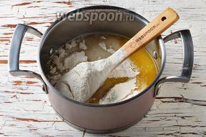 Муку (3,5 стакана) просеять с содой (0,5 ч. л.). Вмешать ложкой муку в тесто.