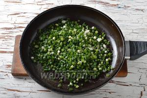 Выложить зелёный лук в горячее сливочное масло и быстро перемешать.