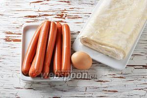 Для работы нам понадобятся сосиски, слоёное бездрожжевое тесто, яйцо.