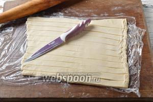 Тесто вынуть из морозильной камеры, разморозить в холодильнике. Раскатать слегка тесто в одну сторону, присыпав сверху небольшим количеством муки. Нарезать полосками, шириной 1,5-2 сантиметра. Длина полосок будет зависеть от того, хотите ли вы заворачивать целую сосиску или половинку. Заворачивать половинки длинных сосисок удобней, а при подаче они смотрятся аккуратней, но выбор только за вами.