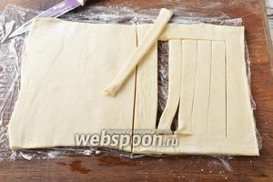 Тесто разморозить и слегка раскатать. Разделить тесто на 2 равные части. У одной части теста вырезать «окошко», а серединку окошка нарезать полосками шириной 1 сантиметр.