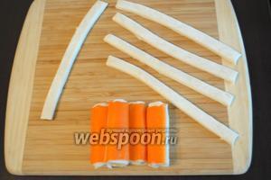 Слоёное тесто 400 г нарезать на полоски. Каждую крабовую палочку обернуть полосками слоёного теста, двигаясь по спирали.