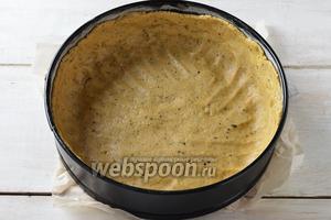 Форму, диаметром 23-24 сантиметра, выложить кулинарной бумагой. Распределить тесто в форме по дну и бортикам (бортики из теста сделать высокими).