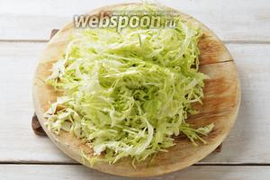 Капусту 400 г промыть, снять верхние листья, вырезать кочерыжку, а остальную капусту очень мелко нашинковать и немного помять.