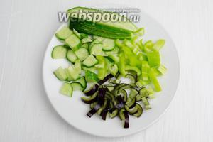 Овощи вымыть, просушить. 1 огурец разрезать вдоль на 4 части, нарезать кусочками. 2 перца очистить от семян, нарезать кусочками.