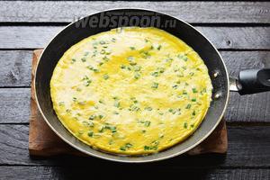 Разогреть сковороду с подсолнечным маслом (1 ч. л.). Вылить яичную смесь в сковороду. Накрыть сковороду крышкой, а огонь уменьшить до минимального. Готовить 5-7 минут, до готовности омлета.