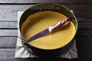 Форму диаметром 24 см выложить пергаментом. На подпыленной мукой доске раскатать большую часть теста в лепёшку, перенести тесто (намотав на скалку) в форму. Сформировать дно и невысокие бортики. Аккуратно обрезать (подровнять) бортики ножом.