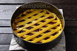 Раскатать меньшую часть теста и вырезать из него полоски шириной 1 см. Выложить полоски на начинку в виде решётки. И смазать 1 желтком.