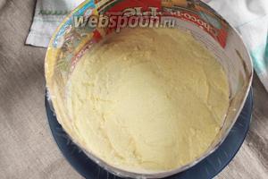 Кулинарное кольцо диаметром 20 см обернуть пищевой пленкой или бумагой для выпечки, чтобы было легче от него освободить торт. На дно кулинарного кольца уложить бисквитный корж. Равномерно на поверхность коржа нанести 2-3 ст. л. крема.