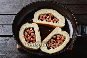 Выложить  подготовленные ломтики хлеба на горячую сковороду, а в отверстия выложить кубики колбасы.